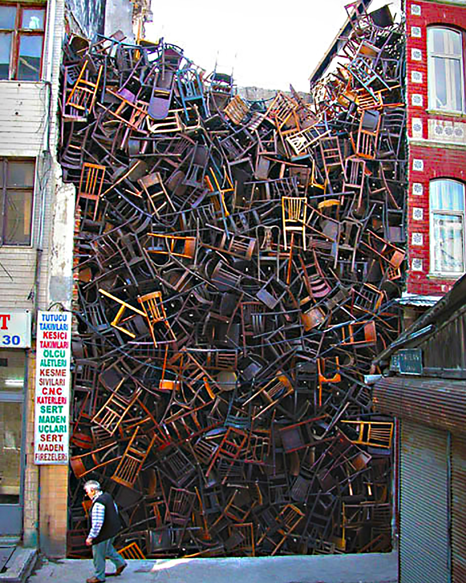 1550 Chairs Stacked Between Two City Buildings (2002) by Doris Salcedo - Pako Campo