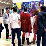 Super-heroes with cape flying over the buildings at Fluorescence Biennale